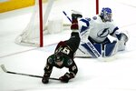 Arizona Coyotes right wing Conor Garland (83) flips over Tampa Bay Lightning goaltender Andrei Vasilevskiy, right, during the second period of an NHL hockey game Saturday, Feb. 22, 2020, in Glendale, Ariz. (AP Photo/Ross D. Franklin)