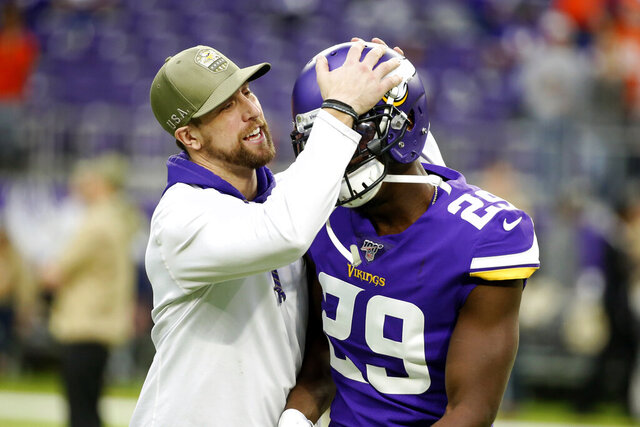 FILE - Injured Minnesota Vikings wide receiver Adam Thielen talks with teammate cornerback Xavier Rhodes (29) before an NFL football game against the Denver Broncos, Sunday, Nov. 17, 2019, in Minneapolis. Rhodes and Thielen came to training camp together as rookies in 2013, one the Vikings first-round draft pick from Florida State, the other an undrafted rookie from Minnesota State.(AP Photo/Bruce Kluckhohn, File)