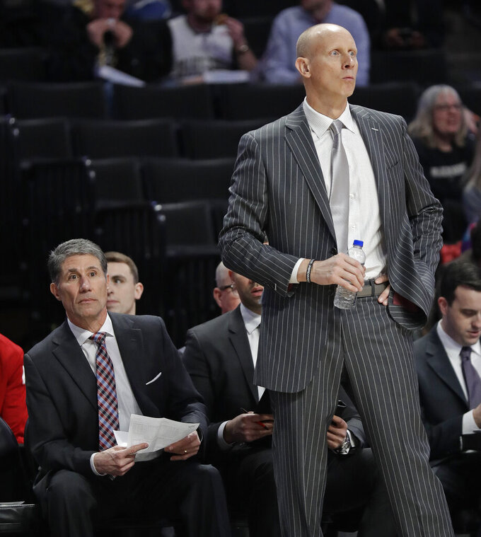 Louisville coach Chris Mack, right, and assistant Dino Gaudio, left, watch during the second half of the team's NCAA college basketball game against Wake Forest in Winston-Salem, N.C., Wednesday, Jan. 30, 2019. (AP Photo/Chuck Burton)