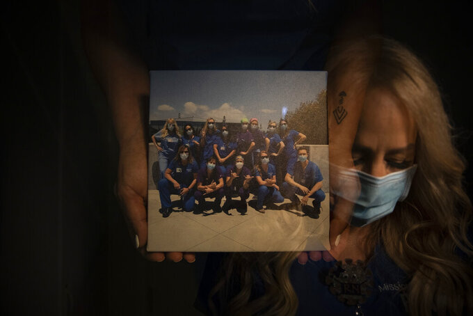 """In this photo created with an in-camera multiple exposure, registered nurse Debbie Wooters, part of a group of nurses who had been treating coronavirus patients in an intensive care unit, holds a group picture taken with her fellow nurses in the empty COVID-19 ICU at Providence Mission Hospital in Mission Viejo, Calif., Tuesday, April 6, 2021. Many patients were frightened when told they would be put on a ventilator. Wooters remembers a patient who """"looked at me and said, through his gasping breath, 'I don't want to die.'"""" (AP Photo/Jae C. Hong)"""