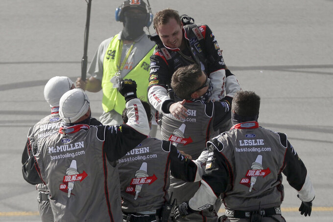 Cole Custer, top, celebrates with his crew after winning a NASCAR Cup Series auto race Sunday, July 12, 2020, in Sparta, Ky. (AP Photo/Mark Humphrey)