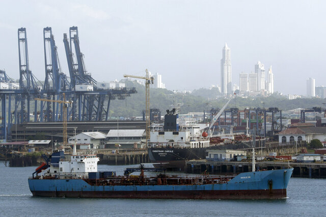 A cargo ship finishes its transit through the Panama Canal on the Pacific side, seen from Panama City, Monday, Jan. 13, 2020. The Panama Canal Authority announced it will start charging customers for their use of fresh water during their transit thought the canal, amid a decrease in rainfall that has lowered lake levels that supply water for human consumption and maritime operations. (AP Photo/Arnulfo Franco)