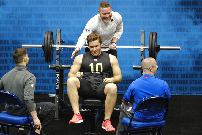 FILE - In this Thursday, Feb. 27, 2020, file photo, Arizona State kicker Michael Turk is congratulated after he bench pressed at the NFL football scouting combine, in Indianapolis. Turk, the nephew of former NFL punter Matt Turk and ex-NFL offensive lineman Daniel Turk, turned heads at the combine when he wowed clubs with his upper-body strength. He recorded 25 reps of the 225-pound bench press, the most by a punter since 2003, per NFL Research. (AJ Mast/AP Images for NFL, File)
