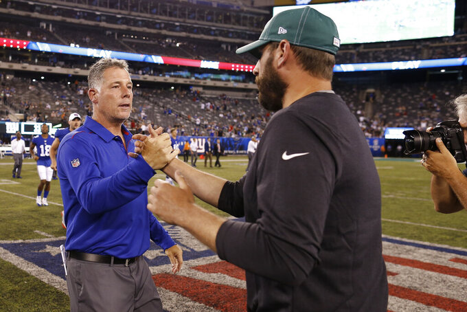 New York Giants coach Pat Shurmur, left, greets New York Jets coach Adam Gase after a preseason NFL football game Thursday, Aug. 8, 2019, in East Rutherford, N.J. The Giants won 31-22. (AP Photo/Adam Hunger)