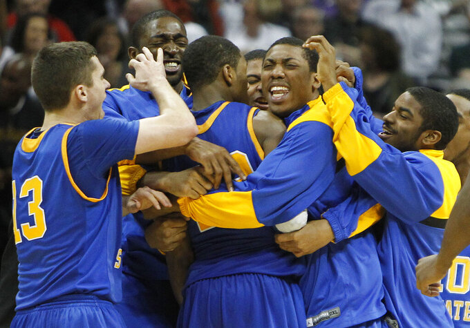 FILE - In this March 17, 2011, file photo, Morehead State players celebrate after beating Louisville 62-61 in a Southwest regional second round NCAA tournament college basketball game in Denver, in this Thursday, March 17, 2011, file photo. Wednesday, March 17, 2021, marked 10 years since Morehead State's first-round upset of No. 4 seed Louisville in its last NCAA appearance. A chance to repeat history looms Friday, March 19, 2021, night when No. 13 Morehead State faces No. 4 West Virginia at Lucas Oil Stadium in Indianapolis. (AP Photo/Ed Andrieski, File)