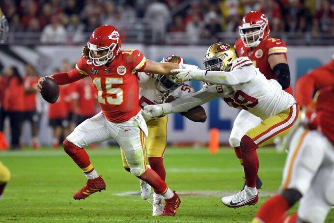 El mariscal de campo de los Chiefs de Kansas City Patrick Mahomes, a la izquierda, intenta escaparse de los jugadores de los 49ers de San Francisco Dee Ford, en el centro, y DeForest Buckner, a la derecha, en la segunda mitad del Super Bowl de la NFL el domingo 2 de febrero de 2020 en Miami Gardens, Florida. (AP Foto/Mark J. Terrill)