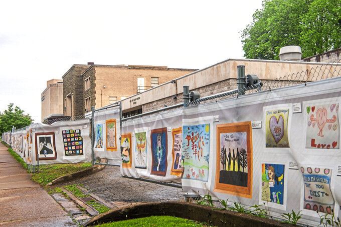 A windscreen installation titled #HeartsTogether: The Art of Rebuilding decorate the perimeter fence of the Tree of Life synagogue, which housed three congregations, New Light, Dor Hadash and Tree of Life, Monday, May 3, 2021, in the Squirrel Hill neighborhood of Pittsburgh. Tree of Life officials last week announced Daniel Libeskind as lead architect for the reconstruction of their synagogue, where in October 2018 a gunman killed 11 worshipers. (Alexandra Wimley/Pittsburgh Post-Gazette via AP)