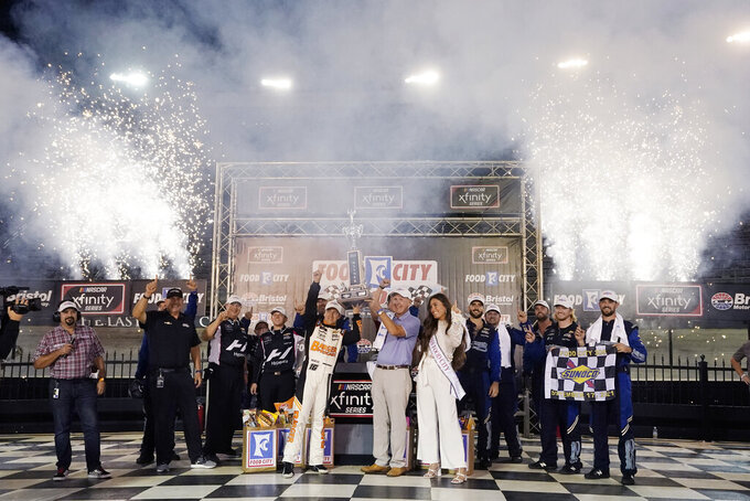 AJ Allmendinger, center left, is presented with his trophy after winning a NASCAR Xfinity Series auto race at Bristol Motor Speedway Friday, Sept. 17, 2021, in Bristol, Tenn. (AP Photo/Mark Humphrey)