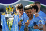 Manchester City's Kyle Walker, right, and John Stones take a selfie with their medals and the English Premier League trophy after the English Premier League soccer match between Brighton and Manchester City at the AMEX Stadium in Brighton, England, Sunday, May 12, 2019. Manchester City defeated Brighton 4-1 to win the championship. (AP Photo/Frank Augstein)