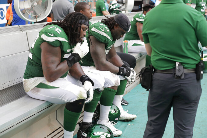 New York Jets offensive tackle Brandon Shell (72) and center Jonotthan Harrison (78) sit on the bench before the end of an NFL football game against the Miami Dolphins, Sunday, Nov. 3, 2019, in Miami Gardens, Fla. (AP Photo/Lynne Sladky)