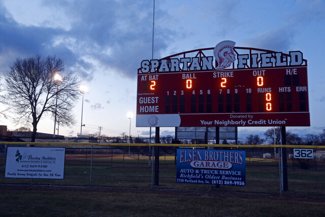 The baseball field scoreboard lights up the year at Richfield High School Wednesday night, April 8, 2020 in Richfield, Minn. Seeking to brighten spirits amid the virus outbreak, the symbolic act of turning on the lights became a movement — fueled by social media with the hashtag #BeTheLight — across the country. (AP Photo/Jim Mone)