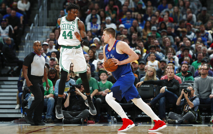Boston Celtics center Robert Williams III, left, jumps up to defend as Denver Nuggets center Nikola Jokic drives during the second half of an NBA basketball game Friday, Nov. 22, 2019, in Denver. The Nuggets won 96-92. (AP Photo/David Zalubowski)