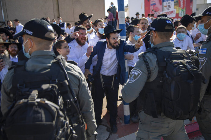 Ultra-Orthodox Jews argue with Israeli border police officers during a protest over the coronavirus lockdown restrictions, in Ashdod, Israel, Sunday, Jan. 24, 2021. As he seeks re-election, Prime Minister Benjamin Netanyahu has turned to a straightforward strategy: Count on the rock-solid support of his ultra-Orthodox political allies and stamp out the coronavirus pandemic with one of the world's most aggressive vaccination campaigns. But with ultra-Orthodox communities openly flouting safety guidelines and violently clashing with police trying to enforce them, this marriage of convenience is turning into a burden. (AP Photo/Oded Balilty)