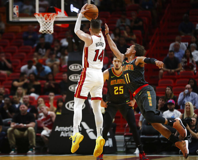 Miami Heat guard Tyler Herro (14) shoots and scores against Atlanta Hawks guard Trae Young (11) during the first half of an NBA preseason basketball game Monday, Oct. 14, 2019, in Miami. (AP Photo/Brynn Anderson)
