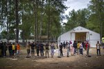 Migrants stand by the fence at the newly built refugee camp in the Rudninkai military training ground, some 38km (23,6 miles) south from Vilnius, Lithuania, Wednesday, Aug. 4, 2021. The Red Cross warned Wednesday that Lithuania's decision to turn away immigrants attempting to cross in from neighboring Belarus does not comply with international law. Lithuania, a member of the European Union, has faced a surge of mostly Iraqi migrants in the past few months. Some 4,090 migrants, most of them from Iraq, have crossed this year from Belarus into Lithuania. (AP Photo/Mindaugas Kulbis)