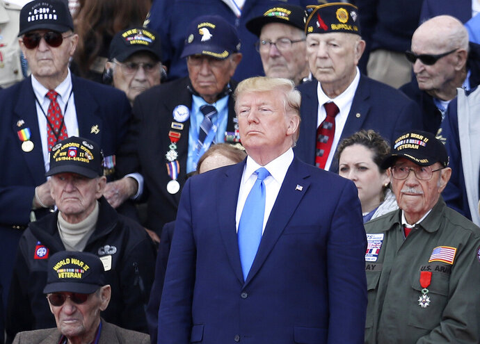 FILE - In this June 6, 2019 file photo, President Donald Trump stands with World War II veterans during a ceremony to mark the 75th anniversary of D-Day at the Normandy American Cemetery in Colleville-sur-Mer, Normandy, France.  A majority of military veterans approve of President Donald Trump's performance as commander-in-chief, reflecting continued support from a group that has strongly backed him throughout his presidency. Still, many veterans believe he doesn't listen enough to military leaders and distrust his decisions on the use of force.  (AP Photo/David Vincent)