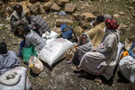 FILE - In this Saturday, May 8, 2021 file photo, an elderly Ethiopian woman sits next to a sack of wheat after it was distributed to her by the Relief Society of Tigray in the town of Agula, in the Tigray region of northern Ethiopia. The United States warned late Thursday, Aug. 19, 2021 that food aid will run out this week for millions of hungry people under a blockade imposed by Ethiopia's government on the embattled Tigray region. (AP Photo/Ben Curtis, File)