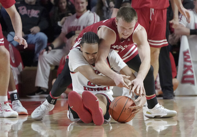 Western Kentucky guard Dalano Banton (20) tries to take control of the ball against Wisconsin guard Brad Davison (34) during the second half of an NCAA college basketball game, Saturday, Dec. 29, 2018, in Bowling Green, Ky. (AP Photo/Tim Broekema)