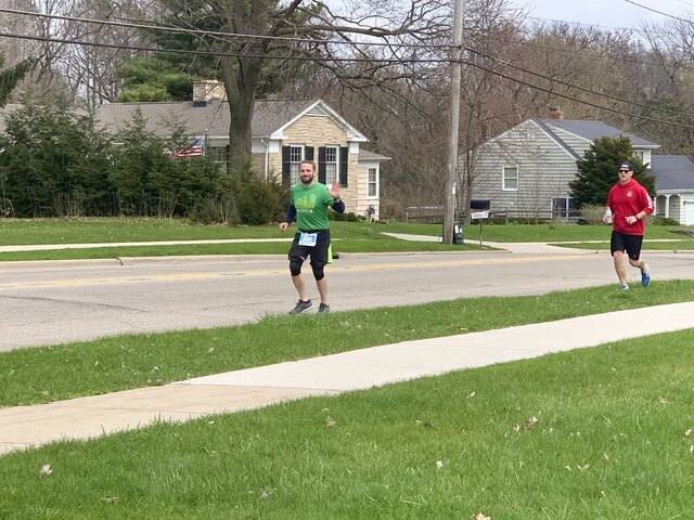 Janesville's Adam Riley gives a wave during the final mile of his marathon Saturday, April 11, 2020, in Janesville, Wis. Riley had signed up to take part in the Milwaukee Marathon, but the race was canceled due to the coronavirus pandemic. Organizers encouraged participants to complete their race 'virtually' at a time and place of their choosing. It was Riley's first marathon. (Eric Schmoldt/The Janesville Gazette via AP)