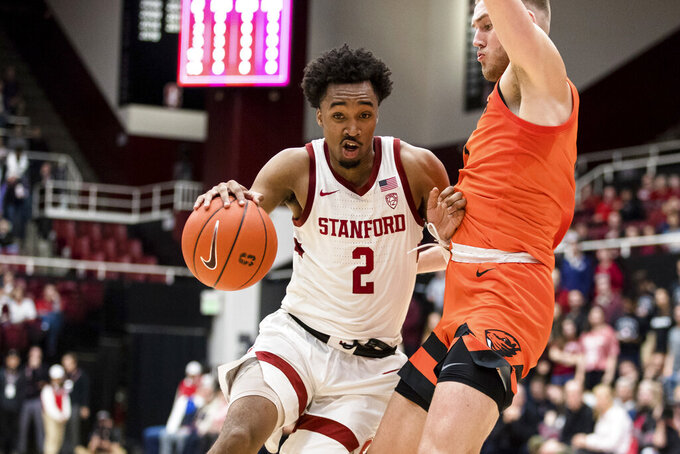 Stanford guard Bryce Wills (2) dribbles as Oregon State forward Tres Tinkle defends during the first half of an NCAA college basketball game Thursday, Jan. 30, 2020, in Stanford, Calif. (AP Photo/John Hefti)