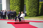German Chancellor Angela Merkel, center right, and Danish Prime Minister Mette Frederiksen, center left, sit on chairs as they listen to the national anthems prior to a meeting at the chancellery in Berlin, Thursday, July 11, 2019. German Chancellor and the visiting Danish prime minister sit through their countries' national anthems at the welcoming ceremony in Berlin, a day after the latest of three incidents in which Merkel's body shook as she stood during similar events. (AP Photo/Markus Schreiber)