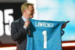Roger Goodell, comisionado de la NFL, sostiene un jersey con el apellido de Trevor Lawrence, reclutado por los Jaguars de Jacksonville como la primera selección del draft, el jueves 29 de abril de 2021, en Cleveland (AP Foto/Tony Dejak)