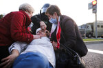 Two women provide a health care to a wounded protester during an opposition rally to protest the presidential inauguration in Minsk, Belarus, Wednesday, Sept. 23, 2020. Belarus President Alexander Lukashenko has been sworn in to his sixth term in office at an inaugural ceremony that was not announced in advance amid weeks of huge protests saying the authoritarian leader's reelection was rigged. Hundreds took to the streets in several cities in the evening to protest the inauguration. (AP Photo)