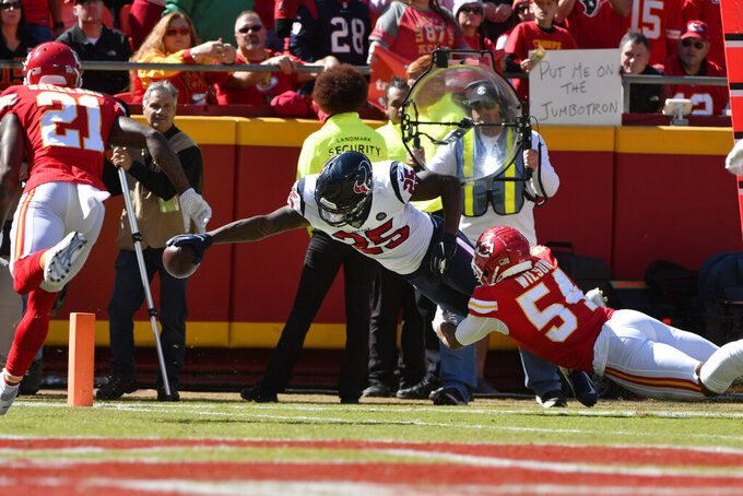 Houston Texans running back Duke Johnson (25) leaps for a touchdown against Kansas City Chiefs linebacker Damien Wilson (54) as cornerback Bashaud Breeland (21) watches during the first half of an NFL football game in Kansas City, Mo., Sunday, Oct. 13, 2019. (AP Photo/Ed Zurga)