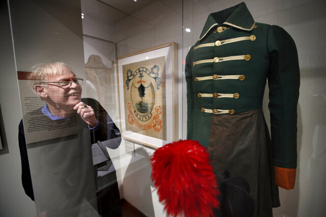 In this Friday, March 13, 2020 photo, State historian Earle Shettleworth examines a First Maine Militia uniform, probably worn by a soldier from Buckfield, on display at the Maine State Museum in Augusta, Maine. The state marked the bicentennial of Maine's liberation from Massachusetts, on March 15, 1820, without a birthday party.The coronavirus forced the state's bicentennial committee to postpone the Sunday, March 15 celebration in Augusta. (AP Photo/Robert F. Bukaty)
