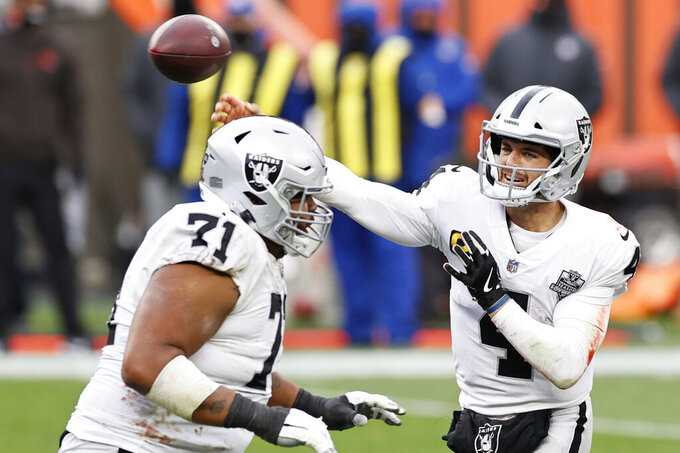 Las Vegas Raiders quarterback Derek Carr (4) throws a 4-yard touchdown pass to wide receiver Hunter Renfrow (13) during the second half of an NFL football game against the Cleveland Browns, Sunday, Nov. 1, 2020, in Cleveland. (AP Photo/Ron Schwane)