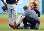 A member of the Cleveland Indians staff checks on starting pitcher Mike Clevinger, right, who fell off the mound while delivering a pitch to the Texas Rangers in the second inning of a baseball game in Arlington, Texas, Monday, June 17, 2019. Clevinger continued playing in the game. (AP Photo/Tony Gutierrez)