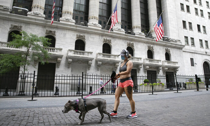 A woman wearing a mask walks her dog past the New York Stock Exchange, Tuesday, June 30, 2020, during the coronavirus pandemic. (AP Photo/Mark Lennihan)