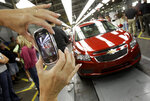 FILE - In this Sept. 8, 2010, file photo, an auto worker takes a picture of the first Chevrolet Cruze compact sedan to come off the assembly line at a ceremony inside the GM factory in Lordstown, Ohio. GM employees in Lordstown and other factories in Michigan and Maryland that are targeted to close within a year say moving will force them to leave behind relatives, even their children, in some cases. (AP Photo/Amy Sancetta, File)