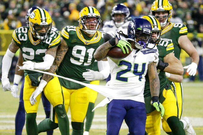 Green Bay Packers' Jaire Alexander (23) and others try to stop Seattle Seahawks' Marshawn Lynch (24) during the first half of an NFL divisional playoff football game Sunday, Jan. 12, 2020, in Green Bay, Wis. (AP Photo/Mike Roemer)