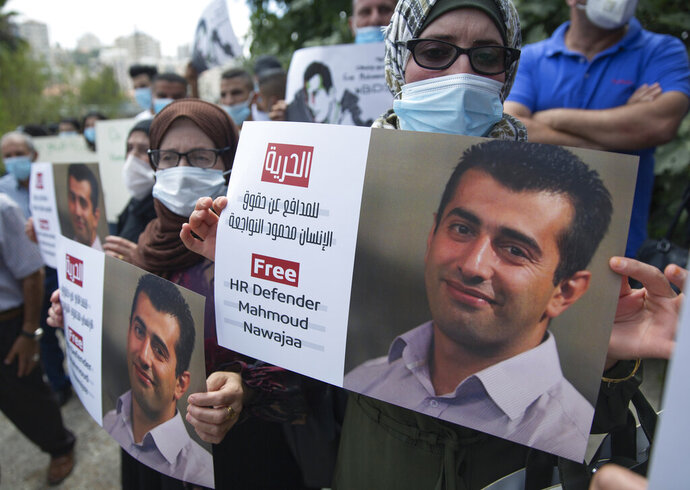 """Palestinians carry posters showing Mahmoud Nawajaa, a leading coordinator of the Palestinian-led boycott movement against Israel, BDS, during a protest calling for the EU to press for his release, in front of the German Representative Office, in the West Bank city of Ramallah, Tuesday, Aug. 11, 2020. The activist was arrested on July 30, remains in Israeli custody and has not been charged. Israel says the arrest is not connected to his boycott activities, and that he is is suspected of unspecified """"security offenses,"""