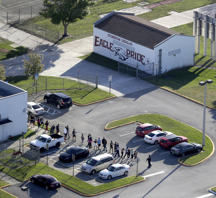 FILE - In this Wednesday, Feb. 14, 2018 file photo, students are evacuated by police from Marjory Stoneman Douglas High School in Parkland, Fla., after a shooter opened fire on the campus. fter a gunman with a history of psychotic behavior killed 17 at a Florida high school two years ago Friday, state lawmakers quickly passed a so-called red flag law that makes it possible for judges, at the request of law enforcement, to ban anyone deemed to be a danger to themselves or others from owning firearms for a year. Florida issued nearly 3,500 risk protective or