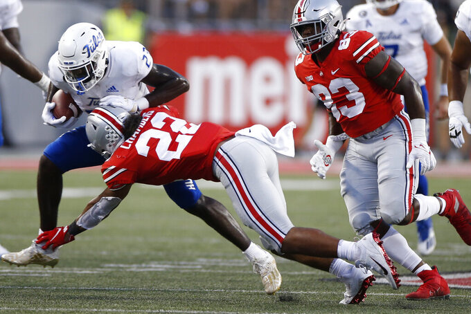 Ohio State linebacker Steele Chambers, front, tackles Tulsa running back Anthony Watkins during the second half of an NCAA college football game Saturday, Sept. 18, 2021, in Columbus, Ohio. (AP Photo/Jay LaPrete)
