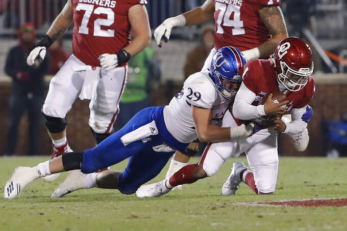 Kansas linebacker Joe Dineen Jr. (29) tackles Oklahoma quarterback Kyler Murray (1) during the first half of an NCAA college football game in Norman, Okla., Saturday, Nov. 17, 2018. (AP Photo/Alonzo Adams)