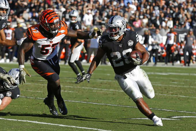 Oakland Raiders running back Josh Jacobs runs with the ball past Cincinnati Bengals linebacker Germaine Pratt (57) during the first half of an NFL football game in Oakland, Calif., Sunday, Nov. 17, 2019. (AP Photo/D. Ross Cameron)