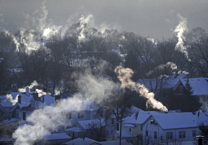 FILE- In this Wednesday Jan. 30, 2019, file photo smoke rises from the chimneys of homes in St. Paul, Minn. Americans burned a record amount of energy in 2018, with a 10% jump in consumption from booming natural gas helping to lead the way, the U.S. Energy Information Administration says. Overall consumption of all kinds of fuels rose 4% year on year, the largest such increase in eight years, a report this week from the agency said. Fossil fuels in all accounted for 80% of Americans' energy use. (Brian Peterson/Star Tribune via AP, File)