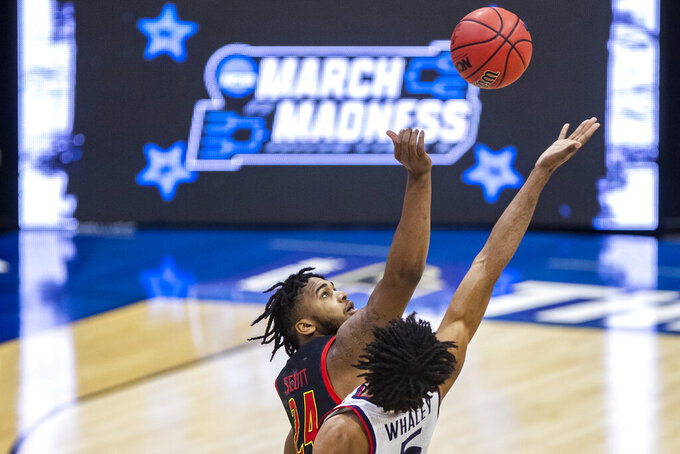 Maryland's Eric Ayala (5) and Connecticut's Isaiah Whaley (5) reach for the opening tip of a first-round game in the NCAA men's college basketball tournament Saturday, March 20, 2021, at Mackey Arena in West Lafayette, Ind. (AP Photo/Robert Franklin)