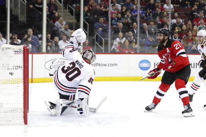 New Jersey Devils right wing Kyle Palmieri (21) scores a goal on Chicago Blackhawks goaltender Cam Ward (30) during the second period of an NHL hockey game, Monday, Jan. 14, 2019, in Newark, N.J. (AP Photo/Julio Cortez)