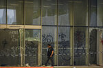 A policeman walks past broken glass panels damaged by protesters at the closed Legislative Council building in Hong Kong, Wednesday, July 3, 2019. A pro-democracy lawmaker who tried to stop Hong Kong protesters from breaking into the legislature this week says China will likely use the vandalizing of the building as a reason to step up pressure on the Chinese territory. (AP Photo/Andy Wong)