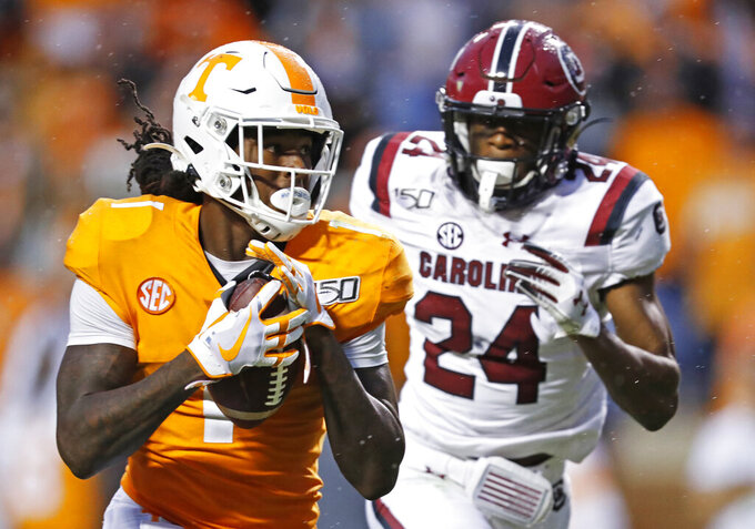Tennessee wide receiver Marquez Callaway (1) catches a pass and runs for a touchdown as he's chased by South Carolina defensive back Israel Mukuamu (24) in the second half of an NCAA college football game Saturday, Oct. 26, 2019, in Knoxville, Tenn. (AP Photo/Wade Payne)