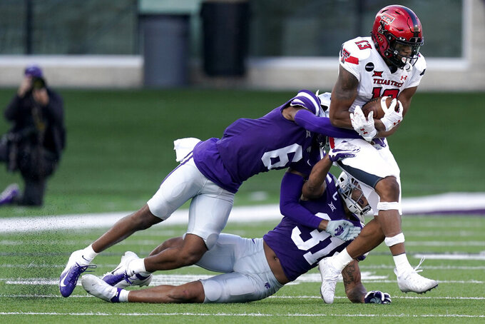 Kansas State defensive backs Justin Gardner (6) and Jahron McPherson (31) tackle Texas Tech wide receiver Erik Ezukanma (13) during the second half of an NCAA college football game Saturday, Oct. 3, 2020, in Manhattan, Kan. (AP Photo/Charlie Riedel)