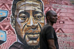 "A local resident stands next to a mural painted in June 2020 showing George Floyd with the Swahili word ""Haki"" or ""Justice"" in the Kibera low-income neighborhood of Nairobi, Kenya, Wednesday, April 21, 2021. After three weeks of testimony, the trial of the former police officer charged with killing George Floyd ended swiftly: barely over a day of jury deliberations, then just minutes for the verdicts to be read — guilty, guilty and guilty — and Derek Chauvin was handcuffed and taken away to prison. The guilty verdict in the George Floyd trial was not just America's victory. It signaled hope for those seeking racial justice and fighting police brutality across the Atlantic. (AP Photo/Brian Inganga)"