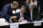 European Council President Donald Tusk, left, and European Commissioner for European Neighborhood Policy Johannes Hahn, right, speak with Serbian President Aleksander Vucic, center, during a round table meeting of EU and Western Balkan heads of state at the National Palace of Culture in Sofia, Bulgaria, Thursday, May 17, 2018. (AP Photo Virginia Mayo, Pool)