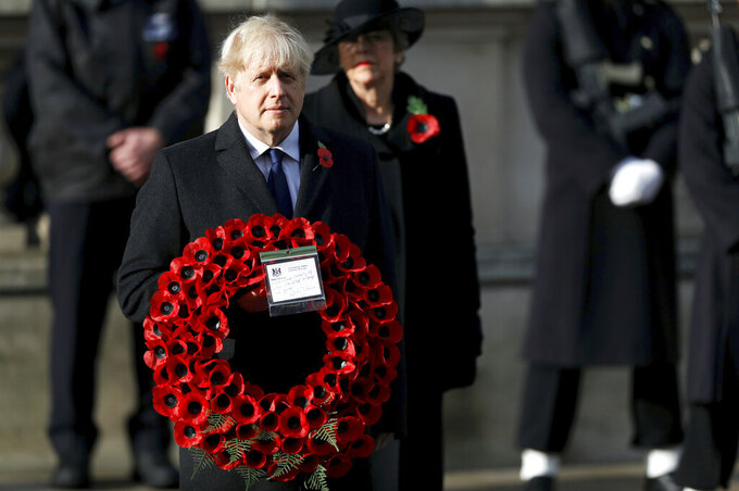 Britian's Prime Minister Boris Johnson carries a wreath, during the Remembrance Sunday service at the Cenotaph, in Whitehall, London, Sunday Nov. 8, 2020. (Peter Nicholls/Pool Photo via AP)