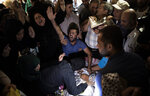 FILE - In this Sunday, Aug. 25, 2019, photo, relatives of Palestinian activist Tamer Sultan, 38 years old, mourn over his body during his funeral in the town of Beit Lahiya, northern Gaza Strip. The death abroad of a Palestinian who fled the Gaza Strip seeking a better life in Europe has highlighted the exodus of thousands of middle-class residents in recent years. Tamer al-Sultan's friends and family say he fled the oppressive rule of Hamas. Others are leaving because of the dire conditions in the territory, which has been under an Israeli and Egyptian blockade since the Islamic militant group seized power 12 years ago. (AP Photo/Khalil Hamra)
