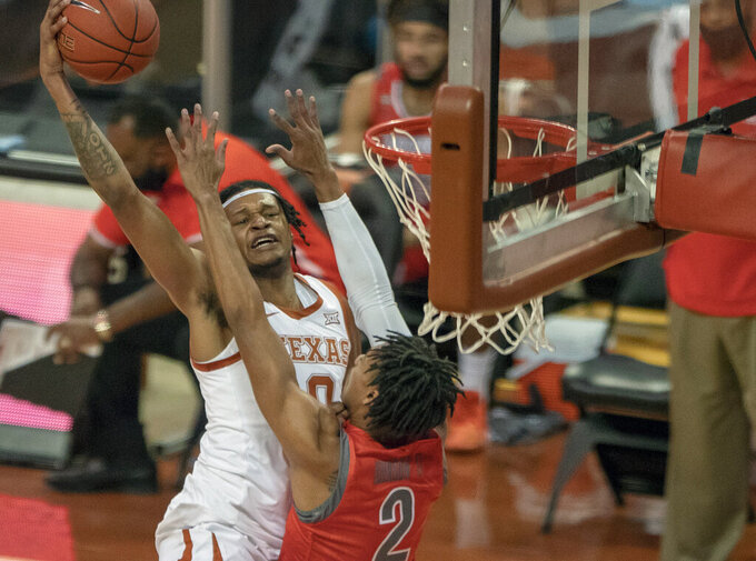 Texas forward Gerald Liddell (0) drives to the basket against Texas Rio Grande Valley's Quinton Johnson II (2) during the first half of an NCAA college basketball game, Wednesday, Nov. 25, 2020 in Austin, Texas. (Ricardo B. Brazziell/Austin American-Statesman via AP)